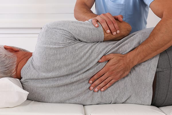 Chiropractor is helping elder guy relax his back pain at their Burnaby Physiotherapy clinic